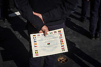 "VALLETTA, MALTA - 8 FEBRUARY 2017: An official of the Libyan Navy Coastguard holds his certificate of attendance during the graduation ceremony of their first training package, here on the deck of the San Giorgio, an amphibious transport dock of the Italian Navy, in Valetta, Malta, on Febuary 8th 2017.<br /> <br /> As a consequence of the April 2015 Libya migrant shipwrecks, the EU launched a military operation known as European Union Naval Force Mediterranean (EUNAVFOR Med), also known as Operation Sophia, with the aim of neutralising established refugee smuggling routes in the Mediterranean. The aim of this new operation launched by Europe is to undertake systematic efforts to identify, capture and dispose of vessels as well as enabling assets used or suspected of being used by migrant smugglers or traffickers. On 20 June 2016, the Council of the European Union extended Operation Sophia's mandate reinforcing it by supporting the training of the Libyan coastguard.<br /> Thus far, following EUNAVFOR MED operation Sophia's activities, 101 suspected smugglers and traffickers have been apprehended and transferred to the Italian<br /> authorities and 380 boats were removed from the criminal organizations' availability. The Operation has saved 32.081 migrants, among whom 1888 children.<br /> <br /> On February 2nd 2017 Italian Premier Paolo Gentiloni and Prime Minister of the U.N. backed Libyan government Fayez al-Serraj signed a memorandum of understanding on cooperation to combat illegal migration, human trafficking and contraband and on reinforcing the border between Libya and Italy. The following day, as EU leaders meet in Malta for a summit, European Council President Donald Tusk said after talks with Serraj, that ""it is time to close the (migrant) route from Libya to Italy"" and that ""the EU has shown it is able to close the routes of irregular migration, as it has done in the eastern Mediterranean.""  Tusk said the Central Mediterranean route was ""not sustainable either for the EU or for"