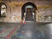 17 MARCH 2015 - BANGKOK, THAILAND: A child, son of a Bangkok firefighter, rides his bike in the entry way of the old Customs House in Bangkok. The old Customs House was once the financial gateway to Thailand (before 1932 called Siam). It was designed by an Italian architect in the 1880s. In the 1950s, customs moved to new, more modern building and the Customs House became the headquarters for the Marine firefighters. The firefighters now live in the decrepit buildings with their families.    PHOTO BY JACK KURTZ