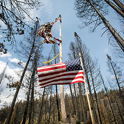 A new American flag sits below another flag which was burned in the Elk Complex fire. The flags are on the property of Robert Bulgin in the Fall Creek area of Elmore County, Idaho. Robert stated that he thought the new flag was placed there by firefighters working the Elk Complex fire which came through the area on August 10th. Thirty eight residences and 43 outbuildings in the Fall Creek area were destroyed by the Elk Complex of fires earlier this month. Wednesday August 28, 2013