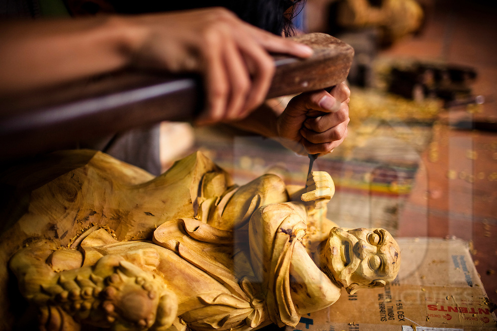 A young man carves a wooden statue at Tan An shop in Hoi An, Vietnam, Southeast Asia