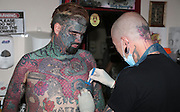 """EXCLUSIVE<br /> Britain's most tattooed man """"King Of Ink Land"""" has had is nipple removed in this latest bizarre twist King of ink as he is now known<br /> spent friday morning having his nipple removed,<br /> <br /> King of ink said """"I have never really found my nipples attractive. In fact I just didn't like them. My girlfriend will miss them as she use to enjoy biting them something that comes a little bit erotica, However I am pleased to finally have them removed. It was not in the least painful however the next week or two I will be a,little sore.<br /> <br /> he went to say<br /> <br /> We will always respect our bodies.<br /> <br /> We believe it is our right to explore our world, both physical and supernatural, through spiritual body modification.<br /> <br /> We promise to always grow as individuals through body modification and what it can teach us about who we are and what we can do.<br /> <br /> We vow to share our experiences openly and honestly in order to promote growth in mind, body, and soul.<br /> <br /> We honor all forms of body modification and those who choose to practice in safe and consensual ways.<br /> <br /> We also promise to respect those who do not choose body modification.<br /> <br /> We support all that join us in our mission and help those seeking us in need of spiritual guidance.<br /> <br /> We strive to share a positive message with everyone we encounter, in order to act as positive role models for future generations in the body modification community.<br /> <br /> We always uphold basic codes of ethics and encourage others to do the same.<br /> when asked about his latest body transformation he replied <br /> <br /> """"I may practice rituals and body modification without prejudice or discrimination. By acting responsibly and with integrity, I wish to observe our sincerely held religious beliefs without restriction""""<br /> <br /> Photo shows: King if Ink pictured with his girlfriend """"Queen of Ink Land"""" and """"Dr Evil Mac"""" or his real na"""