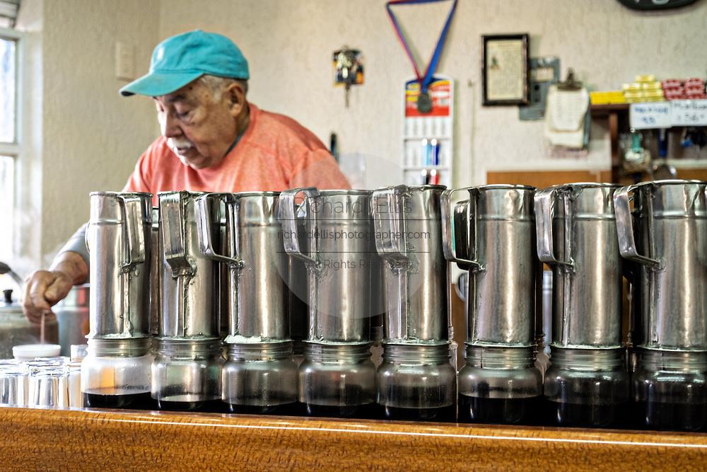A barista makes a cup of coffee standing behind a stack of  cold brew drip coffee pots in Atotonilco de Alto, Mexico.