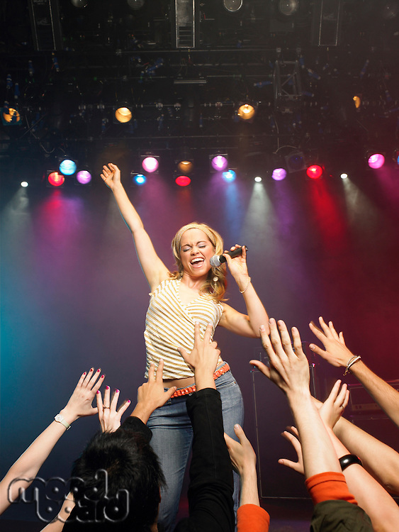 Woman singing in concert on stage in front of adoring fans low angle view