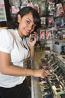 Portrait of young woman using mobile phone in shop