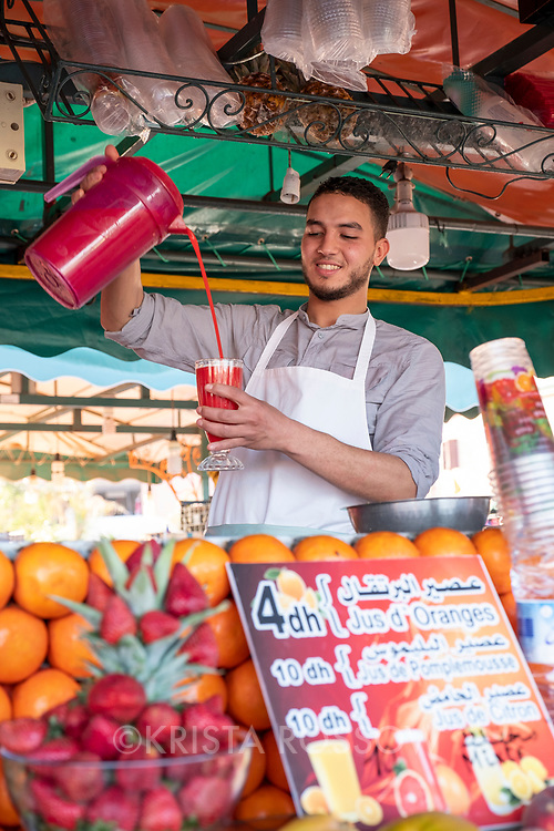 A young man pours juice at a stand in Jemaa el-Fnaa Square, Marrakech, Morocco.