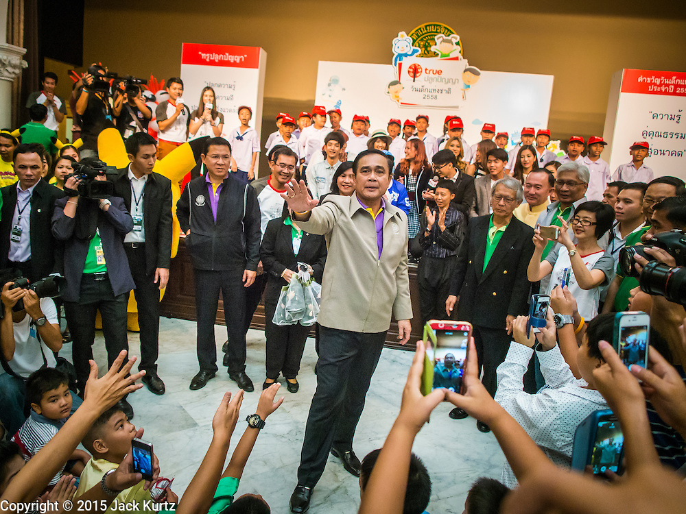 10 JANUARY 2015 - BANGKOK, THAILAND:  General PRAYUTH CHAN-OCHA, the Prime Minister of Thailand, on a leaves a television broadcast with teenagers during National Children's Day celebrations at Government House in Bangkok. National Children's Day falls on the second Saturday of the year. Thai government agencies sponsor child friendly events and the military usually opens army bases to children, who come to play on tanks and artillery pieces. This year Thai Prime Minister General Prayuth Chan-ocha, hosted several events at Government House, the Prime Minister's office.   PHOTO BY JACK KURTZ