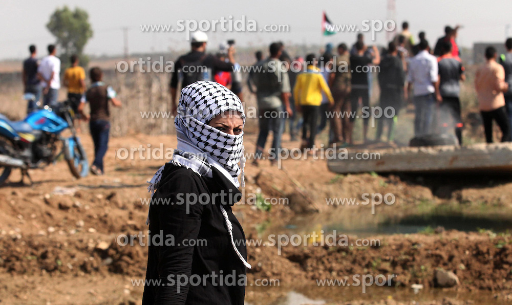 09.10.2015, Gaza city, PSE, Gewalt zwischen Pal&auml;stinensern und Israelis, im Bild Zusammenst&ouml;sse zwischen Pal&auml;stinensischen Demonstranten und Israelischen Sicherheitskr&auml;fte // A female Palestinian protester looks on during clashes with Israeli security forces near the border fence between Israel and the Gaza Strip on October 9, 2015 east of Gaza City. Tension and protests rose after an Israeli man on 09 October stabbed four Palestinians in southern Israel, in what is being seen as a revenge attack, officials said. On 08 October several violent incidents happened, including stabbings which left eight Israelis injured, one Palestinian was killed in East Jerusalem and six in the Gaza Strip in clashes with the army while at least six were injured on the West Bank, Palestine on 2015/10/09. EXPA Pictures &copy; 2015, PhotoCredit: EXPA/ APAimages/ Ashraf Amra<br /> <br /> *****ATTENTION - for AUT, GER, SUI, ITA, POL, CRO, SRB only*****