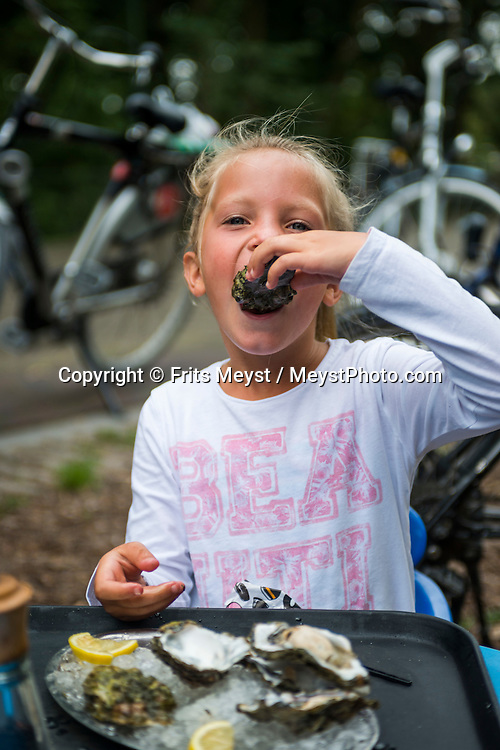 Vlieland, Friesland, Waddenzee, Netherlands, August 2015. A child eating fresh oysters. The Wadden Sea is an intertidal zone in the southeastern part of the North Sea. It lies between the coast of northwestern continental Europe and the range of Frisian Islands, forming a shallow body of water with tidal flats and wetlands. It is rich in biological diversity. In 2009, the  Waddenzee was added to the UNESCO World Heritage List. Photo by Frits Meyst / Meystphoto.com