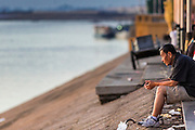 29 JUNE 2013 - PHNOM PENH, CAMBODIA: A man sits by himself in the early morning hours on Sisowath Quay in Phnom Penh.       PHOTO BY JACK KURTZ