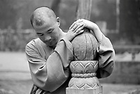 China, Dengfeng, 2007. Lost in thought, a monk's hands echo the shape of infinity, as the head marks the eight precepts of Buddhist practice.