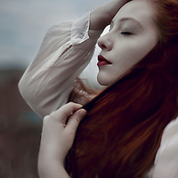 Close up of a girl with red hair and eyes closed