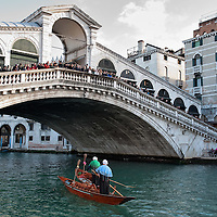 VENICE, ITALY - JANUARY 06:  Two of the participants sail under Rialto Bridge on the Grand Canal dahead of the 34th Befana Regata on January 6, 2012 in Venice, Italy.  In Italian folklore, Befana is an old woman who delivers gifts to children throughout Italy on the feast of the Epiphany on January 6 in a similar way to Saint Nicholas or Santa Claus.