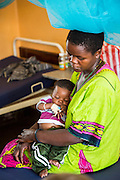 A mother and baby sit on their bed on the children's ward waiting for an examination from Dr Peter O'Reilly, St Walburg's Hospital, Nyangao. Lindi Region, Tanzania.