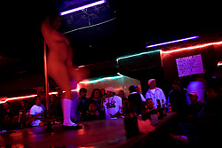 Strippers dance inside a club in Ciudad Juarez, Mexico.  Clubs like these, which double as brothels, have been targeted by drug dealers recently.  Mexico is undergoing a violent war with the nation's drug cartels and Ciudad Juarez has become the murder capital of Mexico, with over 4,000 murders in the past two years.  President Felipe Calderon has dispatched thousands of soldiers and federal police officers in order to contain the situation, but they have not been successful.