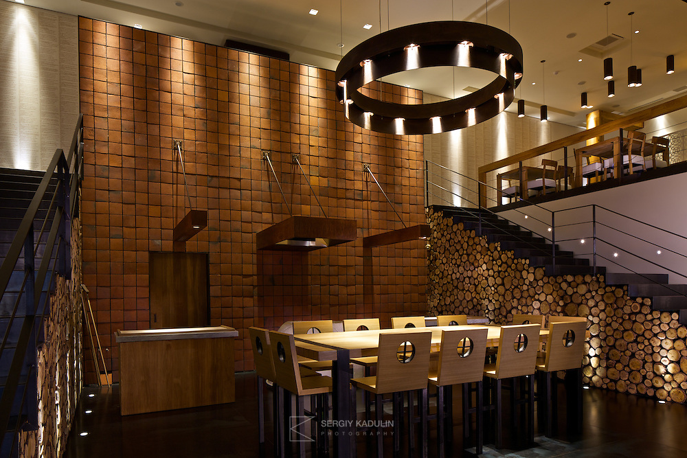 Interior design of georgian restaurant Shoti in Kyiv, Ukraine. View onto brick wall, the oven and dining table in the centre, with steps to the first floor on both sides.