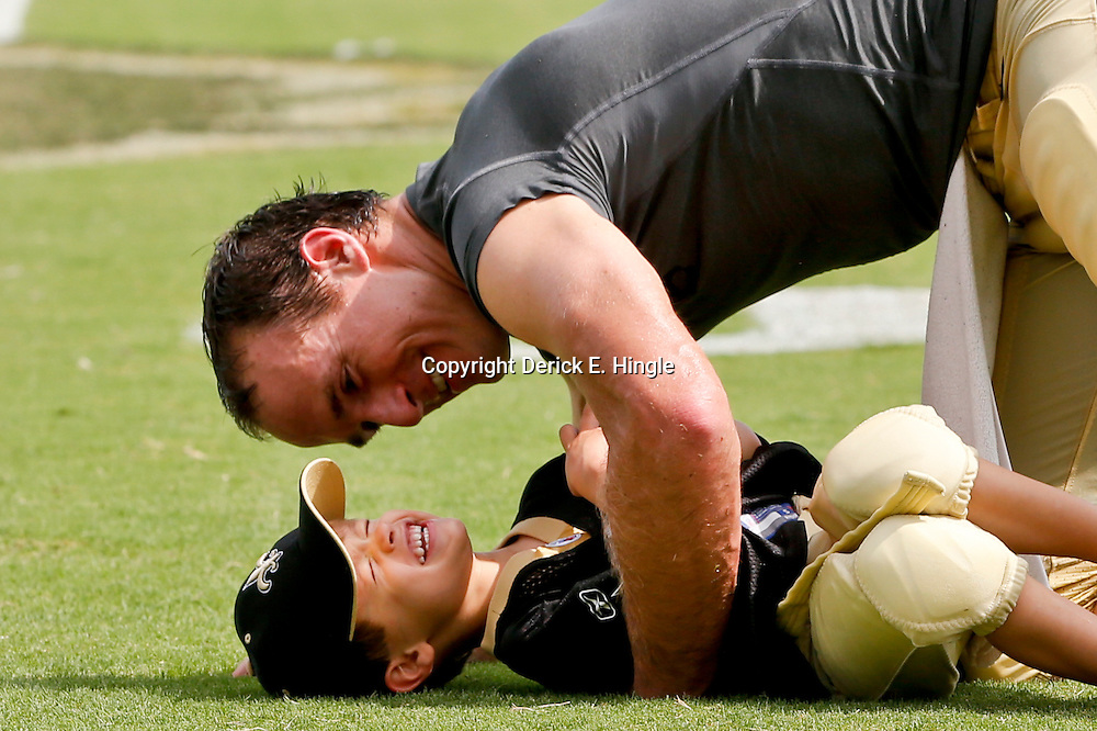 Aug 3, 2013; Metairie, LA, USA; New Orleans Saints quarterback Drew Brees (9) plays with his oldest son Baylen Brees following a scrimmage at the team training facility. Mandatory Credit: Derick E. Hingle-USA TODAY Sports