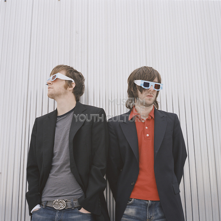 Two young men wearing 3D glasses standing together.