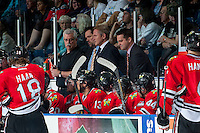 KELOWNA, CANADA - APRIL 25: Mark Brennan, equipment manager, Karl Taylor, assistant coach, Mike Johnston, head coach and Kyle Gustafson, assistant coach, stand on the bench opposite the against the Kelowna Rockets on April 25, 2014 during Game 5 of the third round of WHL Playoffs at Prospera Place in Kelowna, British Columbia, Canada. The Portland Winterhawks won 7 - 3 and took the Western Conference Championship for the fourth year in a row earning them a place in the WHL final.  (Photo by Marissa Baecker/Getty Images)  *** Local Caption *** Mark Brennan; Karl Taylor; Mike Johnston; Kyle Gustasfson;