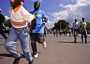07 FEB 96 - PORT AU PRINCE, HAITI: Haitians run through the streets of Port-au-Prince to celebrate the inauguration of  Haitian president Rene Preval Wednesday, Feb 7, 1996. For the first time in Haiti's history, one democratically elected president succeeded another Wednesday, when the tumultous term of President Jean Bertrand Aristide came to an end.  .PHOTO BY JACK KURTZ