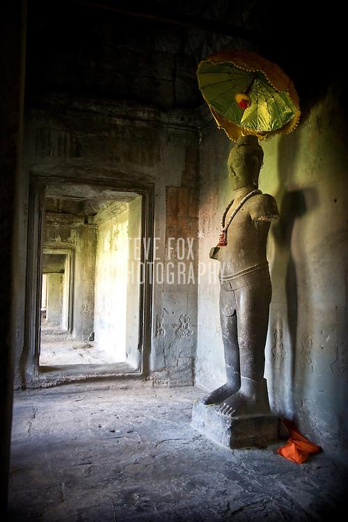 Statue with umbrella at Angkor Wat, Siem Reap, Cambodia