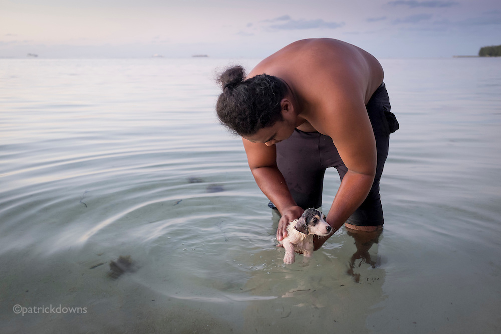 """A local Carolinian man giving his puppy a flea bath in the lagoon on Saipan's west side. Like the Hawaiians use the term """"bra"""" or """"bruddah"""" to refer to people, the Carolinian term is """"bui bui.""""  While people from the Caroline Islands are a minority on Saipan, settling there after typhoons damaged their island, their language is one of the official languages along with Chamorro and English."""