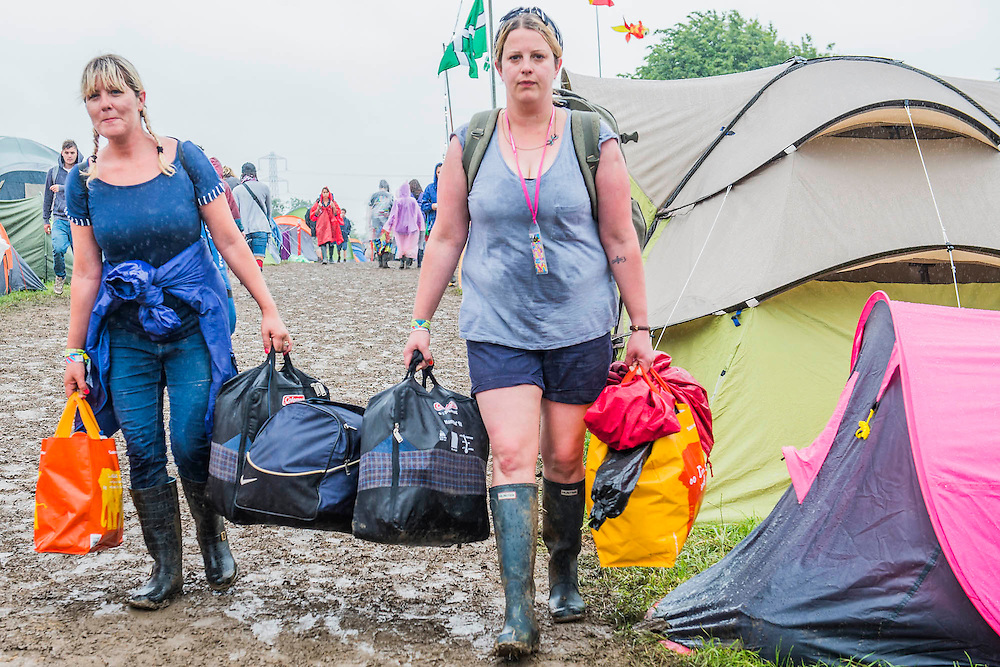 The rain comes down again and people start making an early exit. The 2015 Glastonbury Festival, Worthy Farm, Glastonbury.