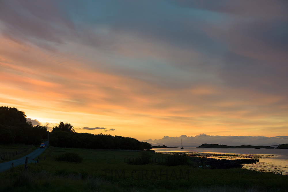 Skyscene of setting sun over solitary fishing boat on Dunvegan Loch as a car is passing on country lane, the Isle of Skye, Scotland