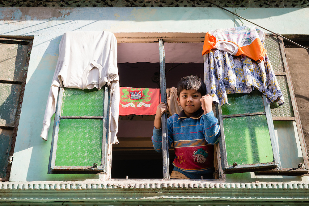 Indian boy at window in the old city of Jaipur