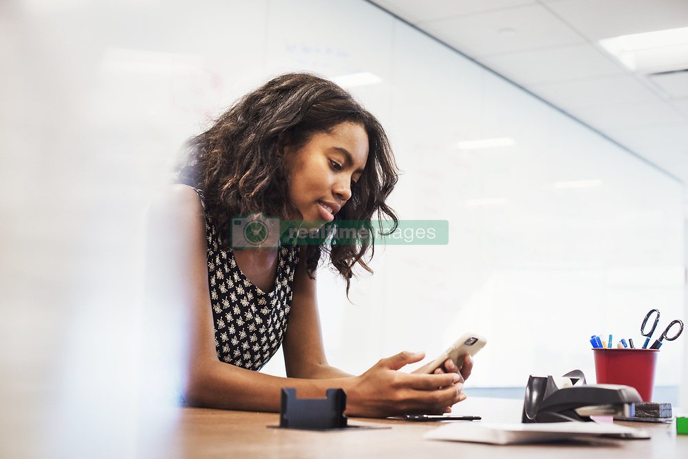 October 23, 2016 - A young woman sitting in a classroom at a table and looking down at a cellphone. (Credit Image: © Mint Images via ZUMA Wire)