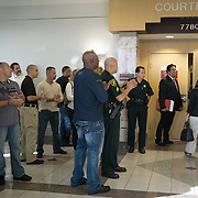 FORT LAUDERDALE, FLORIDA, DECEMBER 21, 2015<br /> Supporters of suspended Broward Sheriff's deputy Peter Peraza, mostly plain clothes and some uniformed officers, clap in support of the officer as he enters the courtroom. This happened just before a brief court appearance by Peraza, seen entering the courtroom with his family and defense team on the right with a grey suit. Peraza faces manslaughter charges in the shooting death of Jermaine McBean, 33, in July of 2013.<br /> (Photo by Angel Valentin/Freelance).