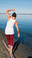 The sun is warm on a clear sunny day at Cordova Beach, Victoria, BC as Taylor balances on a driftwood log.
