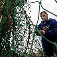 Peter Kendall repairs his fishing net aboard his boat, Miss Alicia, at Rye Harbor, NH. Due to strict fishing regulations, Kendall, like many other local fisherman, is forced not to fish in May. The regulations states that ground fishing is restricted to over 100 miles from shore, which is too far for Kendall's boat. Kendall, a commercial fisherman for 8 years, has been working on his 2 fishing boats to pass the time.