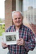 senior man holding an old black and white 1960s family group photo