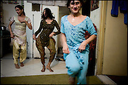 """Chabbou, K. and Kastouri (from the left),  32, 21, 16 years old, transvestites, try a dance. The Guru, Chabbou, has the assignment to educate and to teach to his childs what has learned, from the rules handed down of generation in generation. Evening in Lahore, Pakistan on Monday, December 01 2008.....""""Not men nor women"""". Just Hijira, Kusra. Painted lips, Kajal surrounding their eyes and colourful veils..Pakistan is today considered a strongly, foundamentalist as well, islamic country. But under its reputation, above all over the talebans' continuos advancing, stirs a completely extraneous world, a multiethnic mixed society. Transvestites make part of it, despite this would not be admitted by a strict law. Third gender, the Hijira are born as men (often ermaphrodites) or with an ambiguous genital situation, and they have their testicles and penis removed through a - often brutal - surgical operation. The peculiarity is that this operation does not contemplate the reconstruction of a female organ. This is the reason why they are not considered as men nor women, just Hijira. They are often discriminated, persecuted  and taxed with being men prostitutes in the muslim areas. The members of this chast perform dances during celebrations, especially during weddings, since it is anciently believed that an EUNUCO's dance and kiss in the wedding day brings good luck to the couple's fertility...To protect the identities of the recorded subjects names and specific .places are fictionals."""