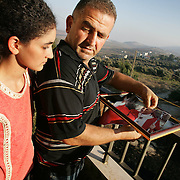 17th August 2006&#xA;Marjayoun, Lebanon&#xA;Post War South Lebanon&#xA;John Butrous and his daughter Coco on the balcony of their home in Marjayoun, sothern Lebanon with a picture of the Pope that was alledgedly torn into four pieces by Israeli troops who broke into their home and used it as a base during recent battles with Hezbollah fighters. Their home overlooks the border with Israel.<br />