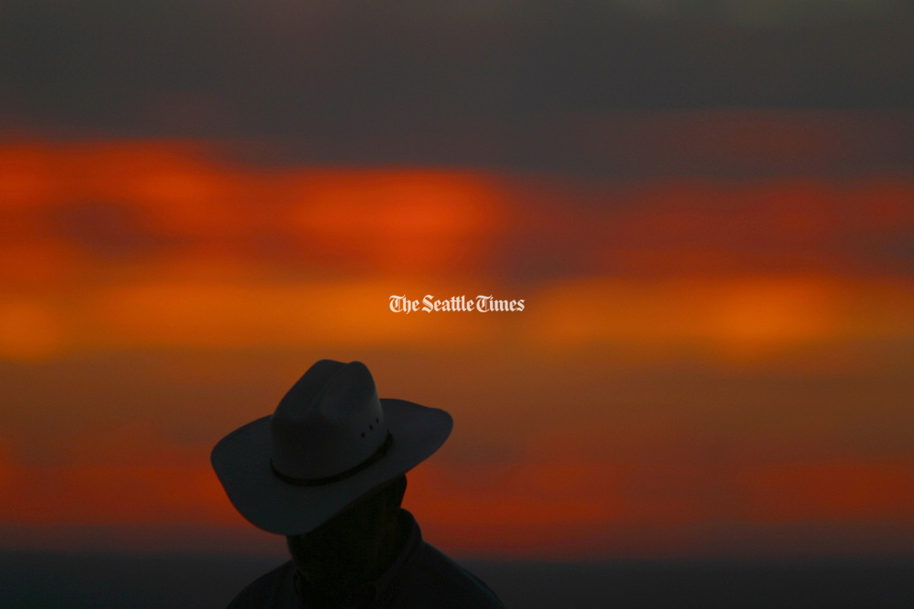 The Palouse offers solitude, which can translate into contentment or loneliness. A Palouse resident takes in the sunset from top of Steptoe Butte. (Tom Reese / The Seattle Times)