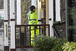 © Licensed to London News Pictures. 22/12/2015. Glenridding UK. Picture shows a police officer warning residents of potential flooding. The village of Glenridding that flooded twice in one week in the last round of bad weather is preparing for more floods after days of heavy rain. Photo credit: Andrew McCaren/LNP