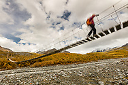 Shaky suspension bridge as hiker crosses over glacial melt streams  in Interior Alaska. Autumn. Morning.