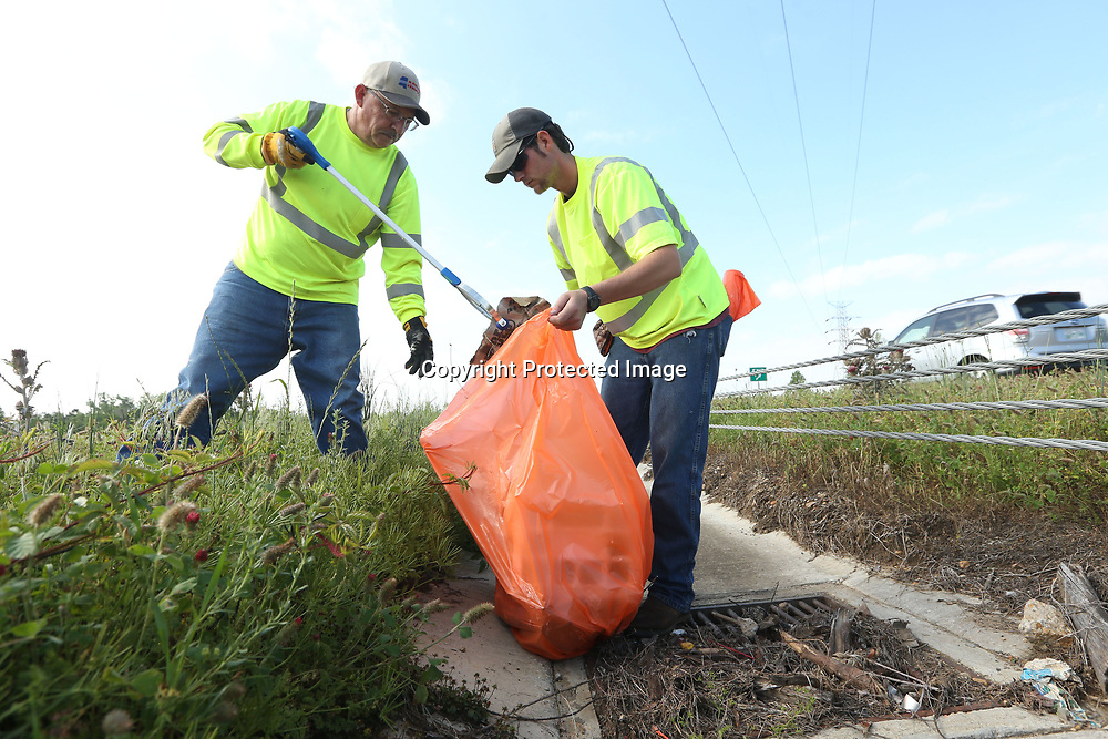 """Doug Hargett and Jay Duncan, maintenance workers with MDOT, pick up roadside trash in the center lane of Highway 45 near Main Street in Tupelo Wednesday morning. MDOT has partnered with the City of Tupelo for """"Pick it up Tupelo"""", with crews out picking up litter at various intersections throughout Tupelo."""
