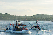 A tradiotnal catamaran fishing boat coming back into Mirissa harbour as a whale watching boat leaves. Whale watching from Mirissa harbour, Sri Lanka.<br />