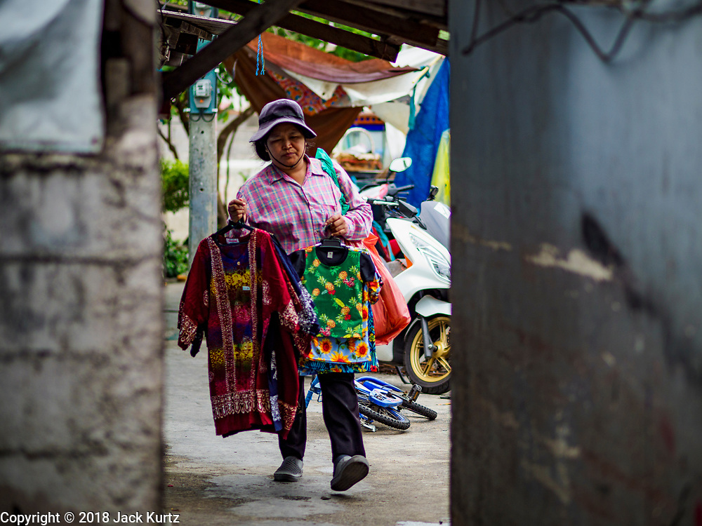 """22 MARCH 2018 - BANGKOK, THAILAND: A vender goes door to door selling clothes along Khlong Lat Phrao. Bangkok officials are evicting about 1,000 families who have set up homes along Khlong  Lat Phrao in Bangkok, the city says they are """"encroaching"""" on the khlong. Although some of the families have been living along the khlong (Thai for """"canal"""") for generations, they don't have title to the property, and the city considers them squatters. The city says the residents are being evicted so the city can build new embankments to control flooding. Most of the residents have agreed to leave, but negotiations over compensation are continuing for residents who can't afford to move.      PHOTO BY JACK KURTZ"""