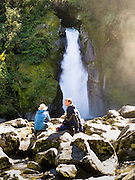 Trampers/hikers enjoy lunch on the rocks at Giants Gate Falls, along the Milford Track, Fiordland National Park, New Zealand