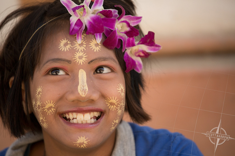 A young Myanmar girl wearing a creative and playful version of the traditional makeup.