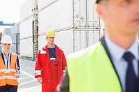 Workers walking in shipping yard