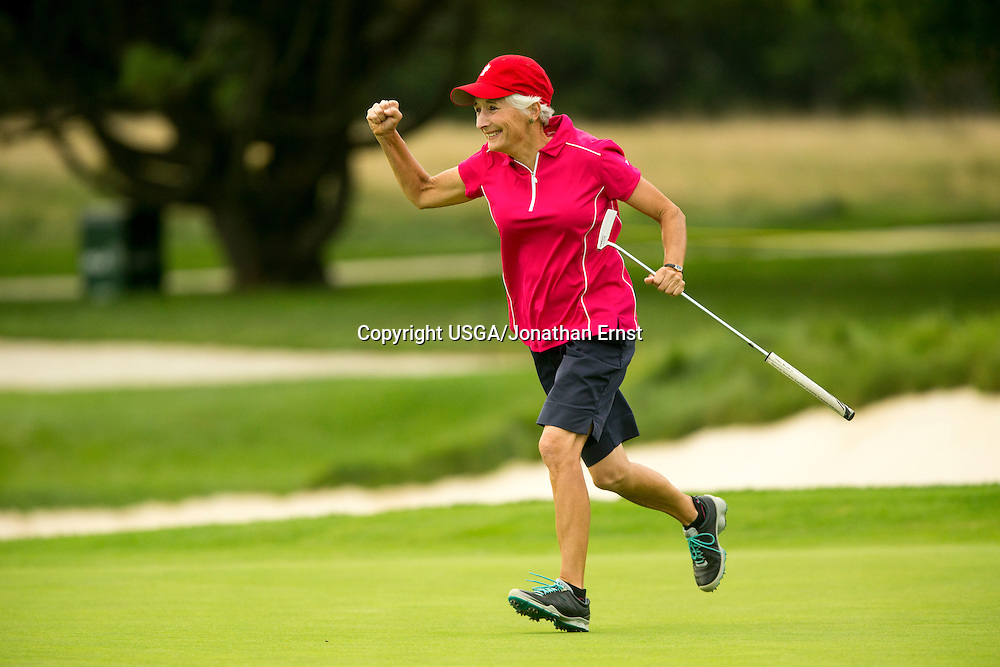 Terri Frohnmayer runs to her caddie after sinking a long putt on the 18th green to win her match against Patricia Brogden, 1 up, during the second round of match play at the 2014 USGA Senior Women's Amateur at Hollywood Golf Club in Deal, N.J.