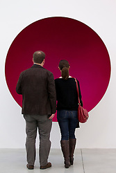 © Licensed to London News Pictures. 09/10/2012. LONDON, UK.  Two gallery visitors view Anish Kapoor's sculpture 'Hollow' (2012) at a press view ahead of his new exhibition at the Lisson Gallery in London today (09/12/12) . The exhibition, the first since the artists solo exhibition at the Royal Academy of the Arts in 2009, features new works by Kapoor and runs from the 10th of October to the 10th of November 2012. Photo credit: Matt Cetti-Roberts/LNP