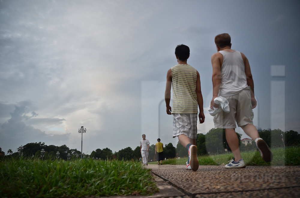 Two men are walking to keep healthy on a path and between patches of grass in front of Ho Chi Minh mausoleum in Hanoi.