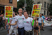 "Jesse Duncan, left, and Marcus Woolen carry signs that read ""20 years together 8 months married finally legal."" They march with Broadway Impact, an organization of theater artists in support of marriage equality."
