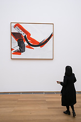Woman looking at painting Hammer and Sickle by Andy Warhol at Hamburger Bahnhof modern art museum in Berlin, Germany