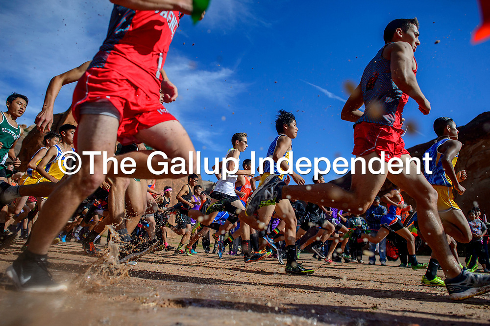 The boys varsity makes their start through the mud during the Gallup Invitational Cross Country meet at Red Rock Park Saturday.